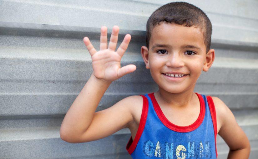 Den leende pojken Zaid gör en high five framför en grå vägg.