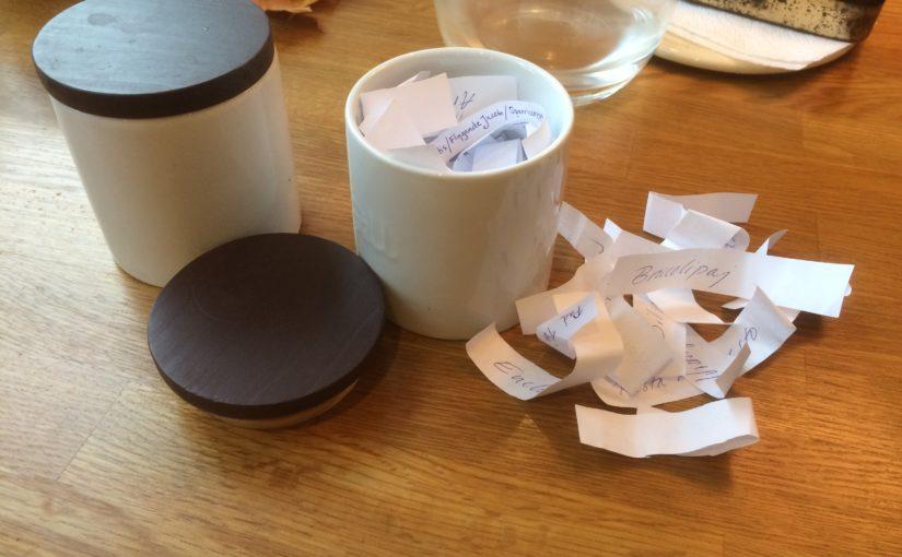 Två burkar i keramik där en är tom och en innehåller små handskrivna lappar med maträtter som funkar för middag på.